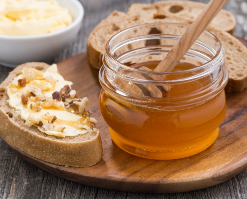 Photo of a jar of honey next to bread with butter, honey, and nuts on top