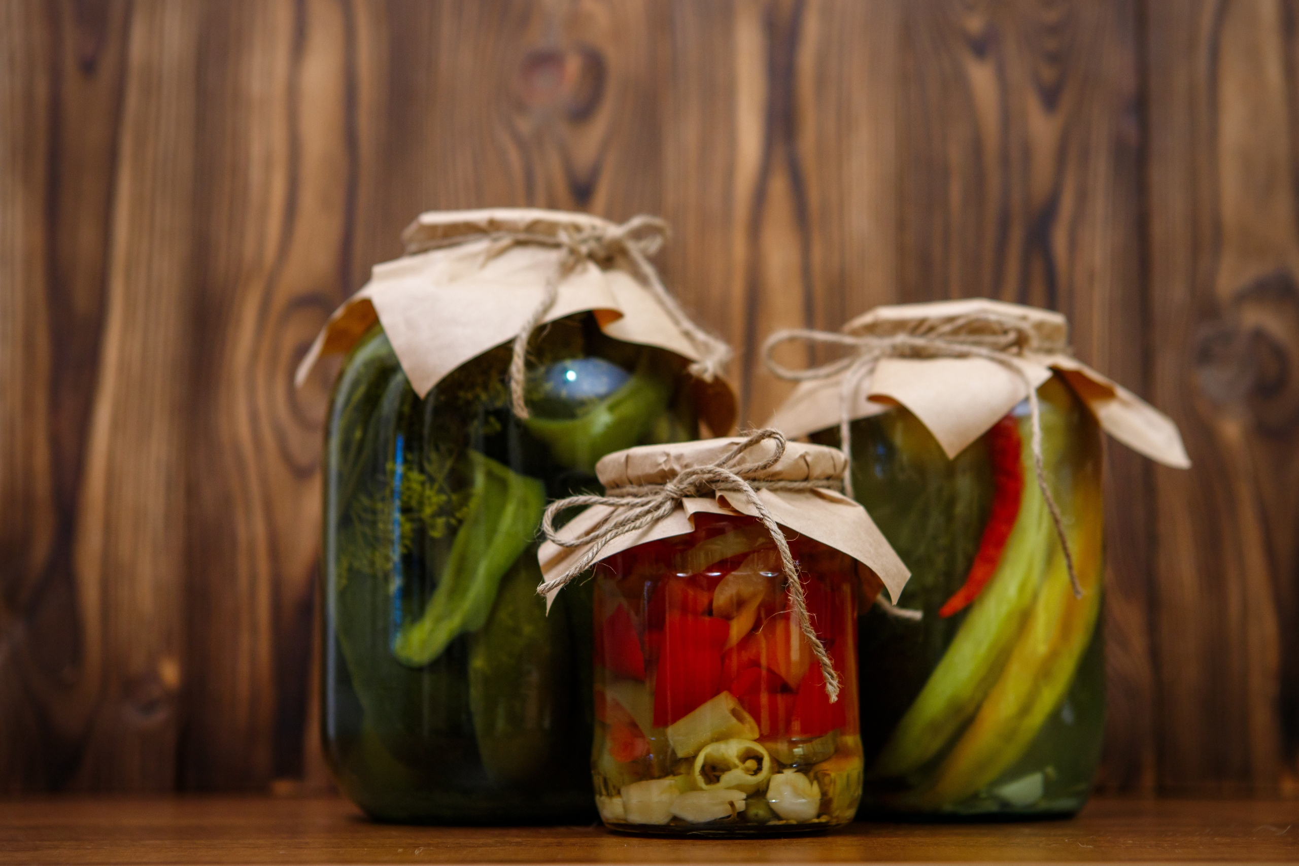 Canned vegetables in glass jars on a wooden background. Pickles. Pickled cucumbers and peppers.