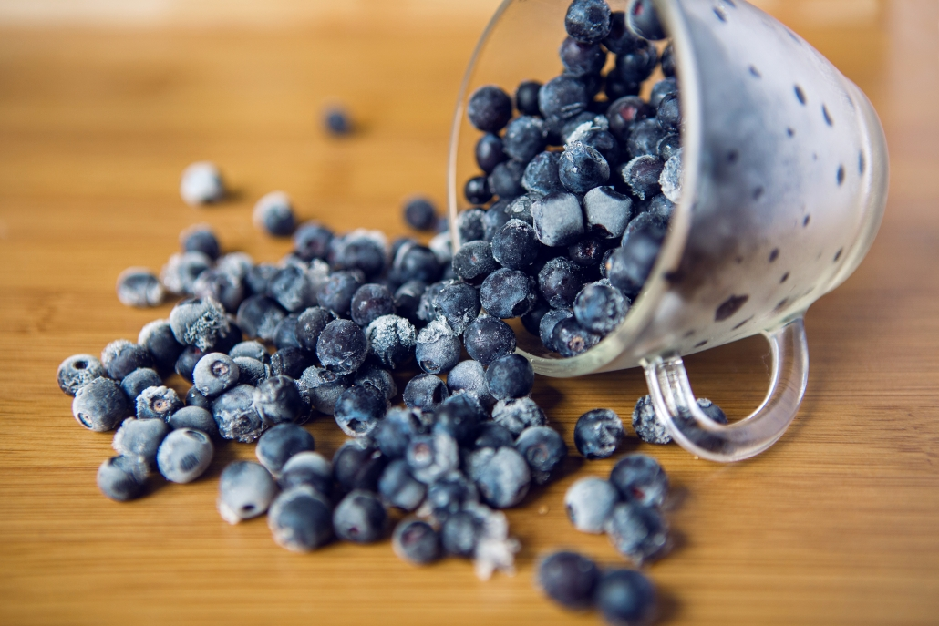 wooden table with frosted clear cup with handle tipped on the side with frozen blueberries spilling out